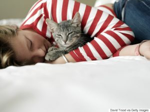 Girl (11-13) lying on bed, embracing cat, eyes closed, close-up